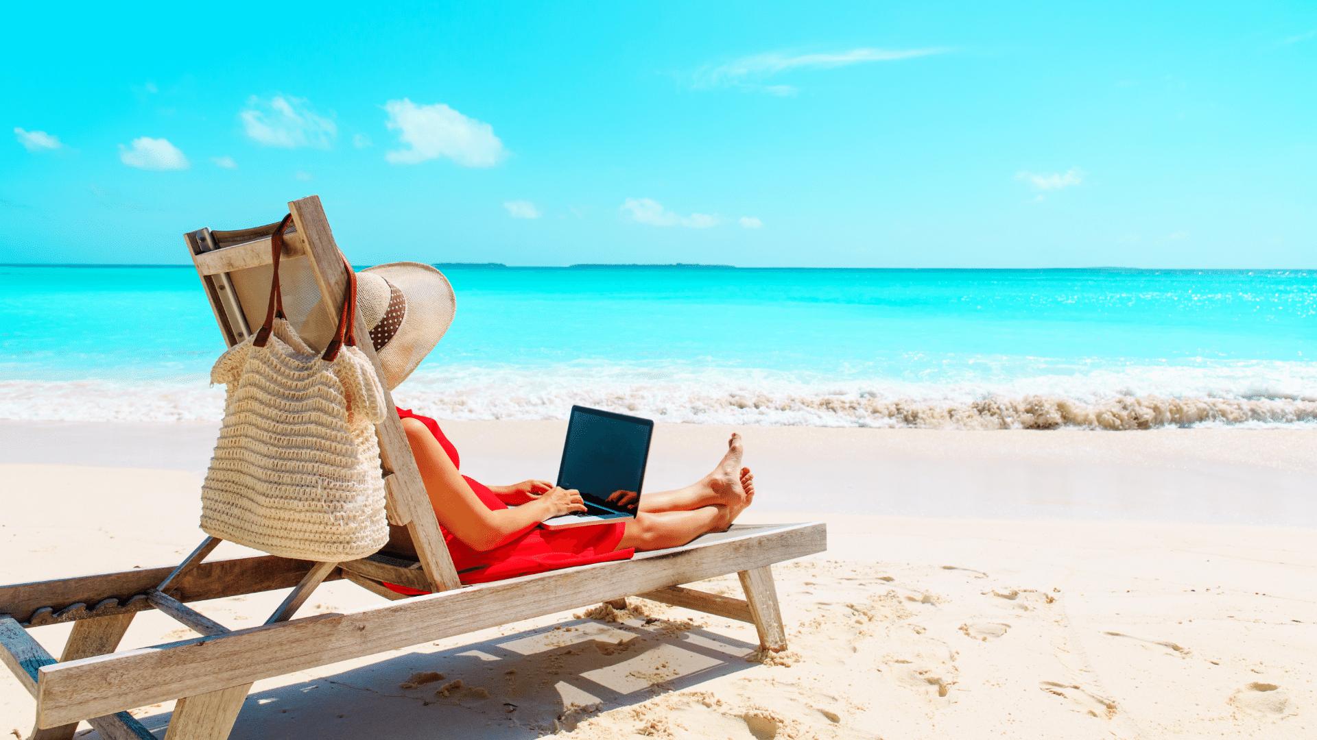 Persona al lavoro al notebook sulla spiaggia